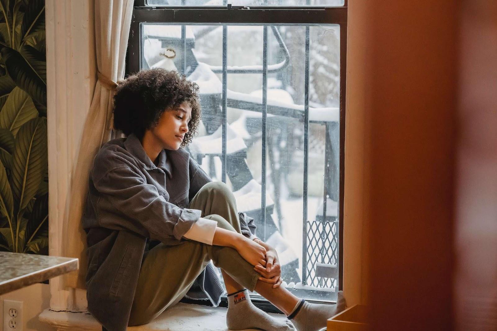 Sad woman sitting in windowsill