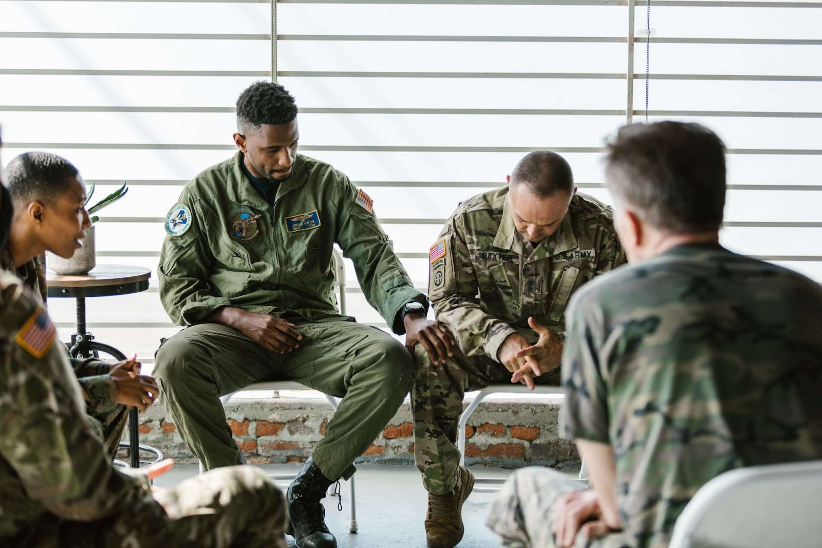 A group of military members, possibly veterans, in group therapy