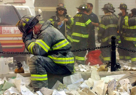 FDNY and NYPD are first responders who showed up to the scene of the World Trade Centers on the morning of September 11, 2001. Fireman shown kneeling in debris filled with emotion of the horrible scene he is witnessing of the Twin Towers collapsed. Image courtesy of irishcentral.com.