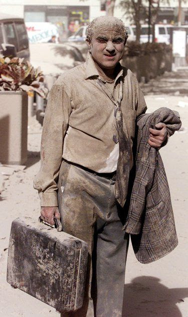 A survivor pictured covered in white dust, trying to escape the clouds of dust. Photographer Stan Honda captured this image on September 11, 2001, of Edward Fine, who was an owner of an investment and public relations firm. Edward Fine was on the 78th floor of 1 World Trade Center when it was hit. Image courtesy of news.yahoo.com.