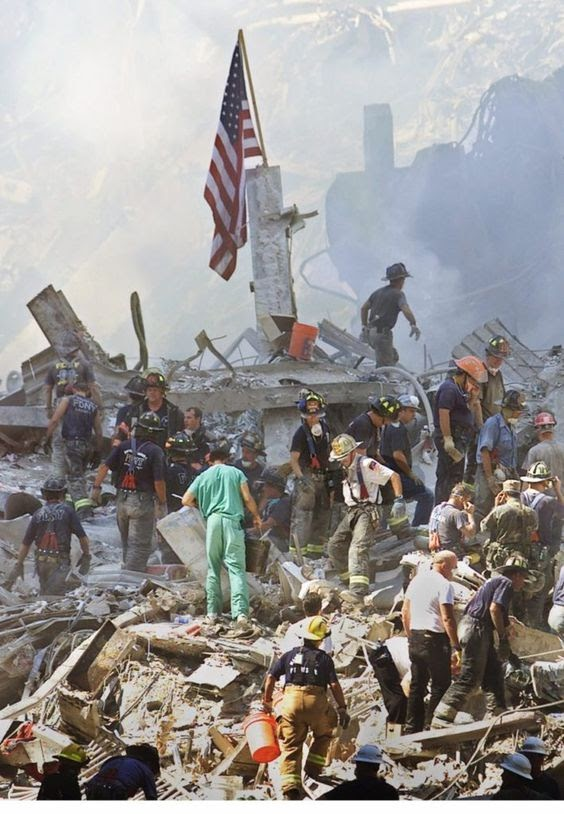 Firefighters, volunteers, EMT, and police officers digging through the rubble and debris of the fallen Twin Towers in hopes of recovering survivors. Image courtesy of breitbart.com.