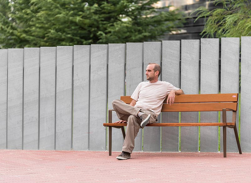 Man sitting on wooden bench with fence in background
