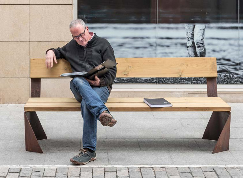 Man sat on modern wooden and metal park bench