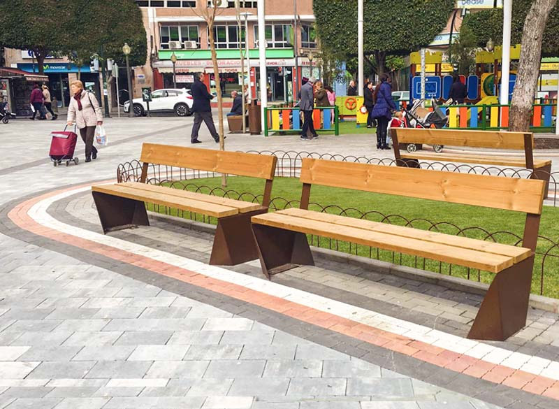 Wooden communal bench with rust effect metal frame in urban area