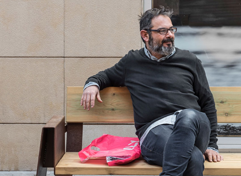 Man sat on modern wood and metal bench with shopping bag