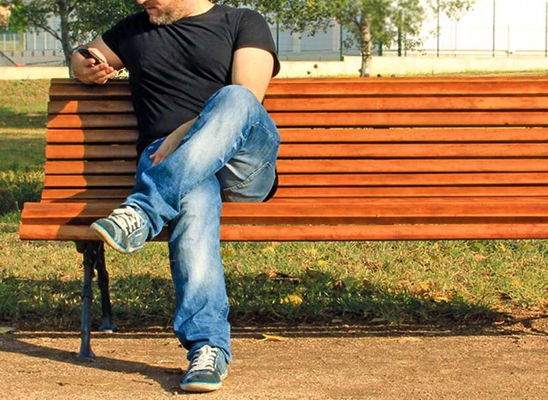 Man sat on multiple slatted park bench
