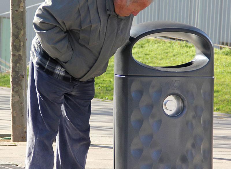 Durable plastic outdoor public litter bin with man looking inside