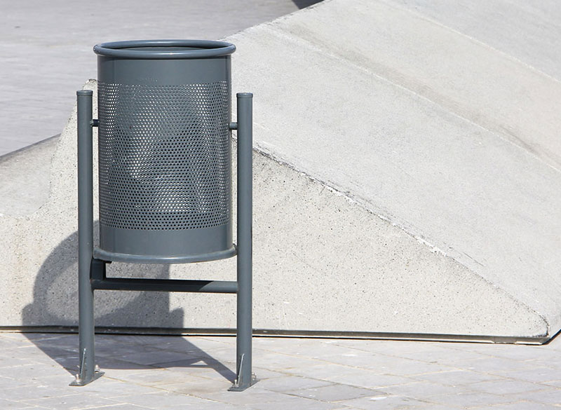 Circular metal outdoor public litter bin with perforated design
