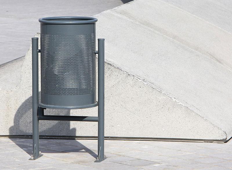 Circular metal outdoor public litter bin with perforated design