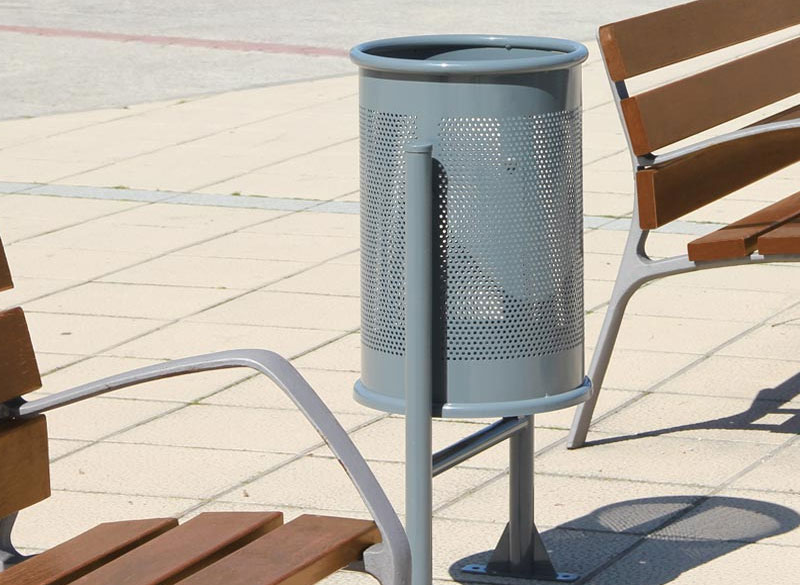 Circular metal outdoor public litter bin with perforated design and park benches