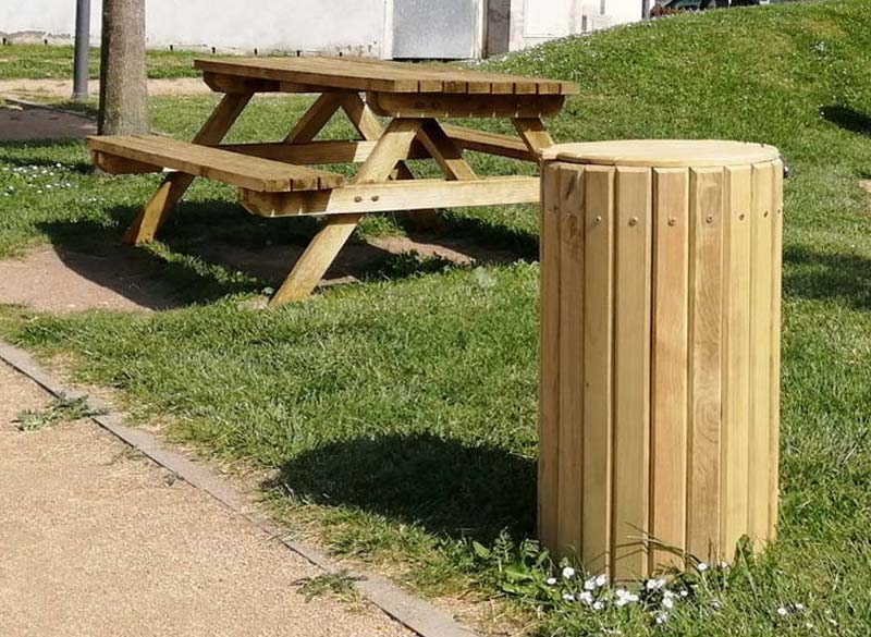 Wooden outside litter bin with lid for parks and public spaces with picnic bench in background