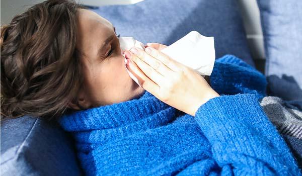 nurse blowing nose flu season carerev