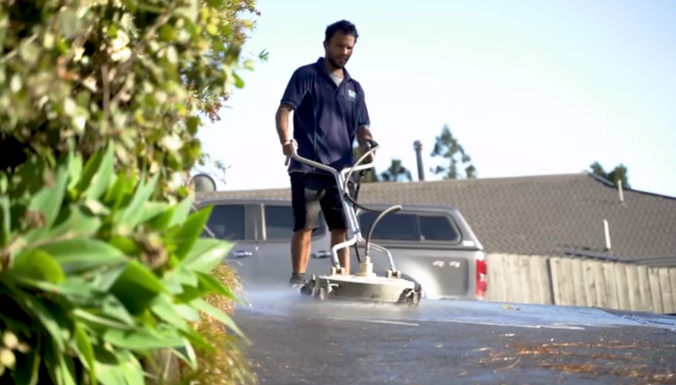 Cleaning concrete paths with water blaster in Whangarei