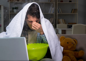man breathing steam out of a bowl to try and treat his sinus infection
