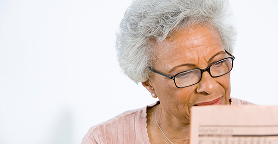 senior woman looking at stock pages in newspaper