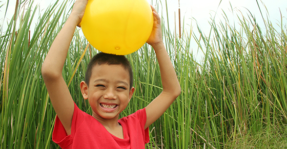 smiling boy holding yellow ball over his head