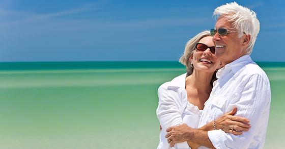 senior couple smiling at beach