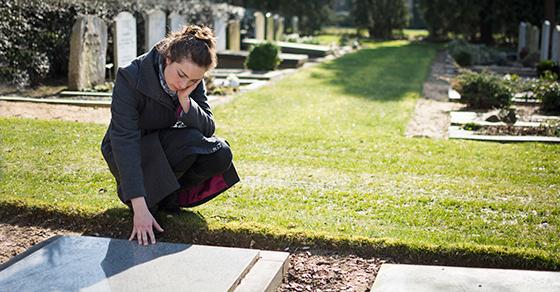 woman kneeling beside grave