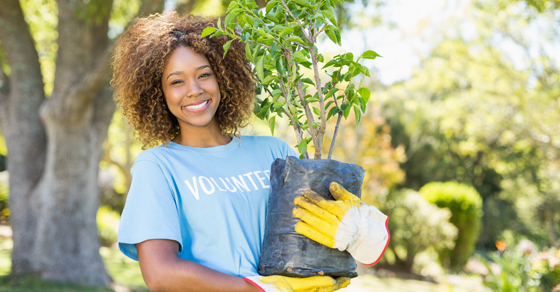 young woman in volunteer shirt holding a sapling