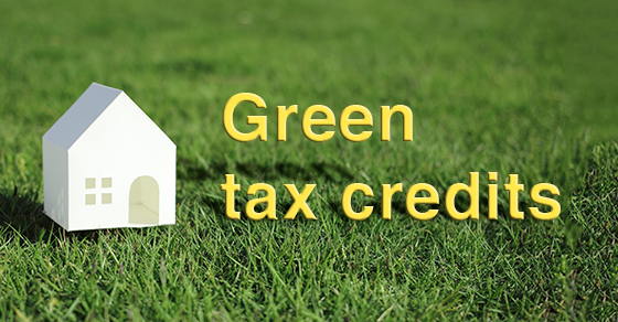 """""""green tax credits"""" letters on lawn next to small white house"""