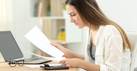 woman looking at financial paperwork