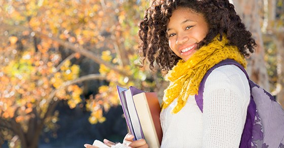 young woman with backpack and books