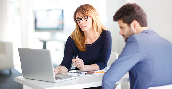 woman and man looking at financials on laptop