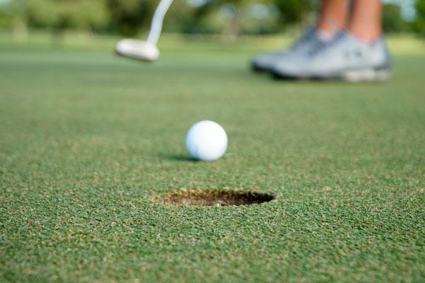 golf ball putt into hole