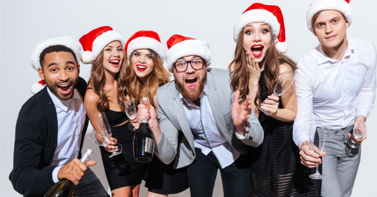 happy coworkers wearing santa hats