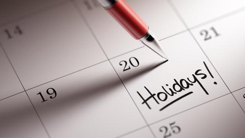 "pen on a calendar that reads ""holidays"""