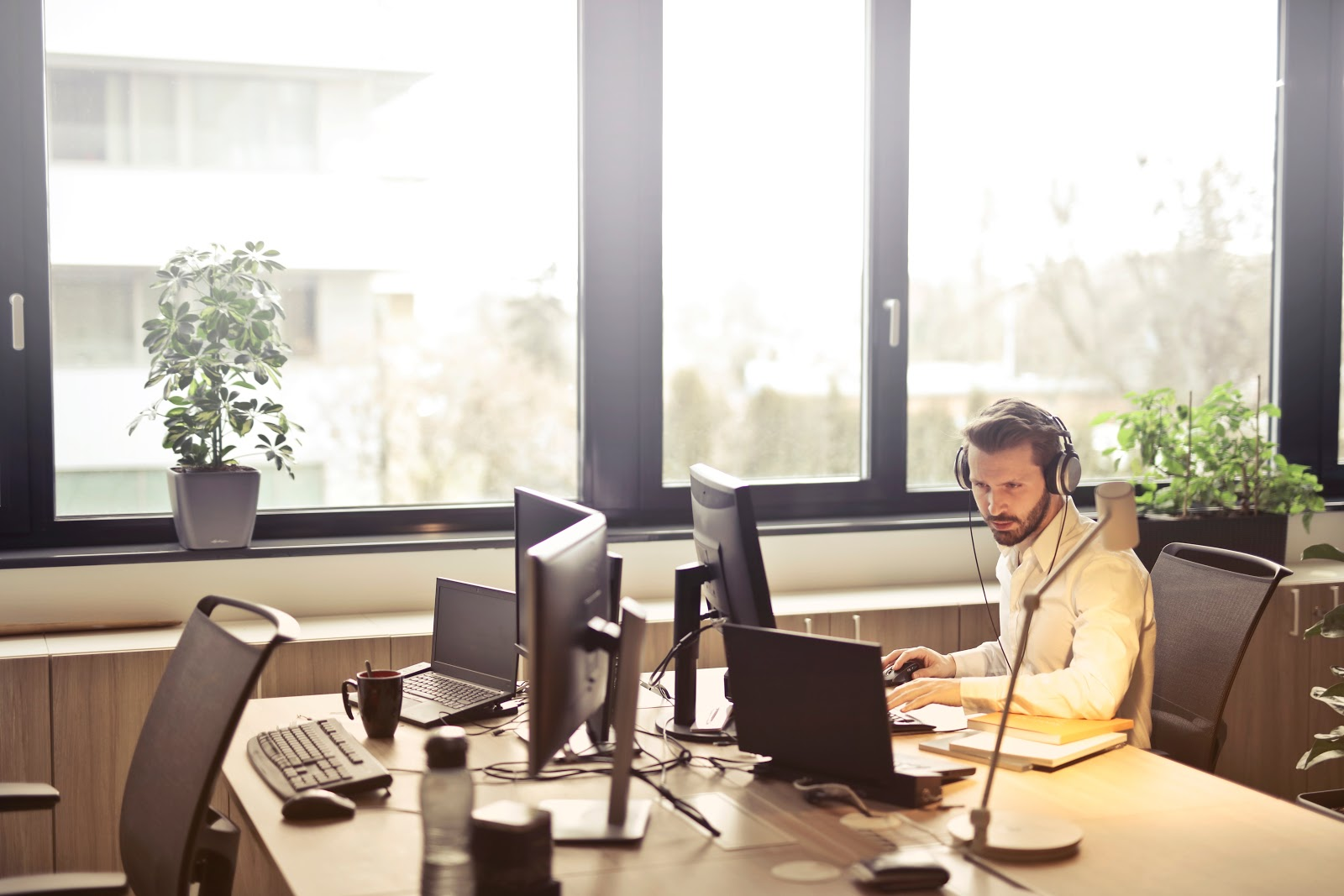 Man wearing headphones at computer in front of large window