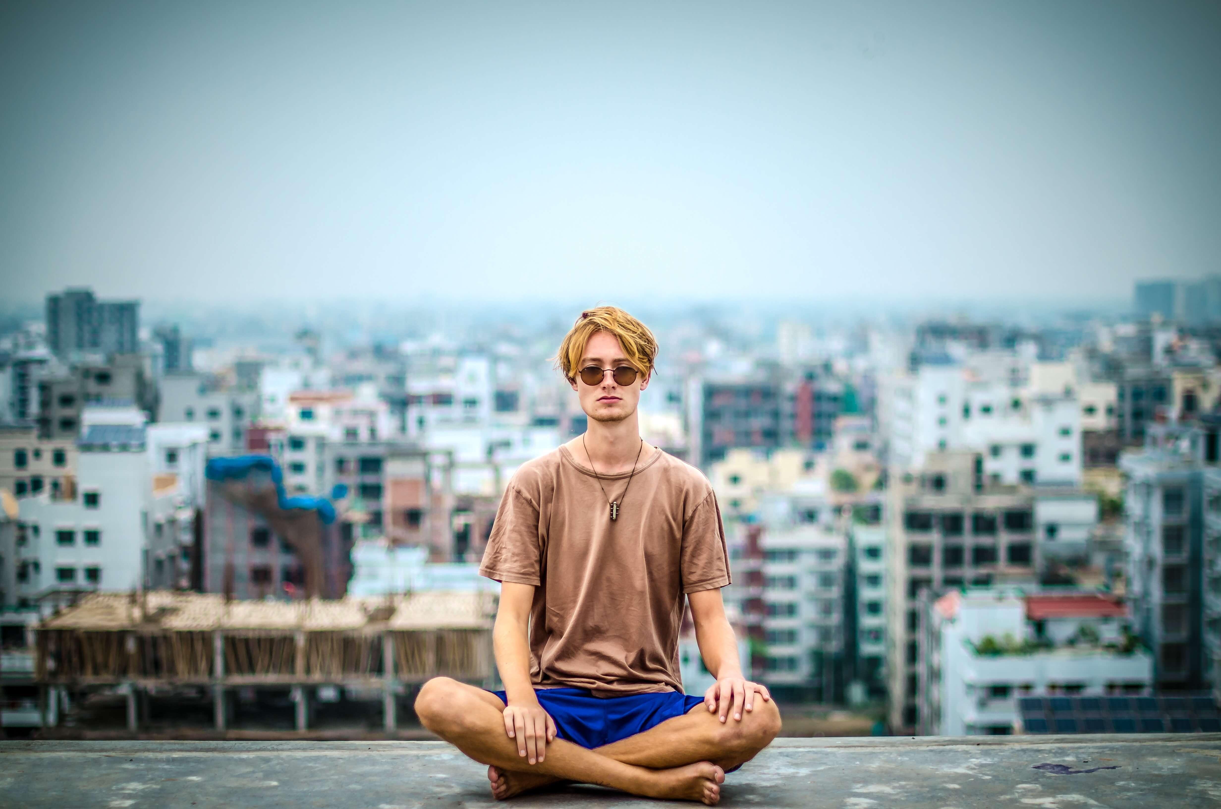 man meditating in city