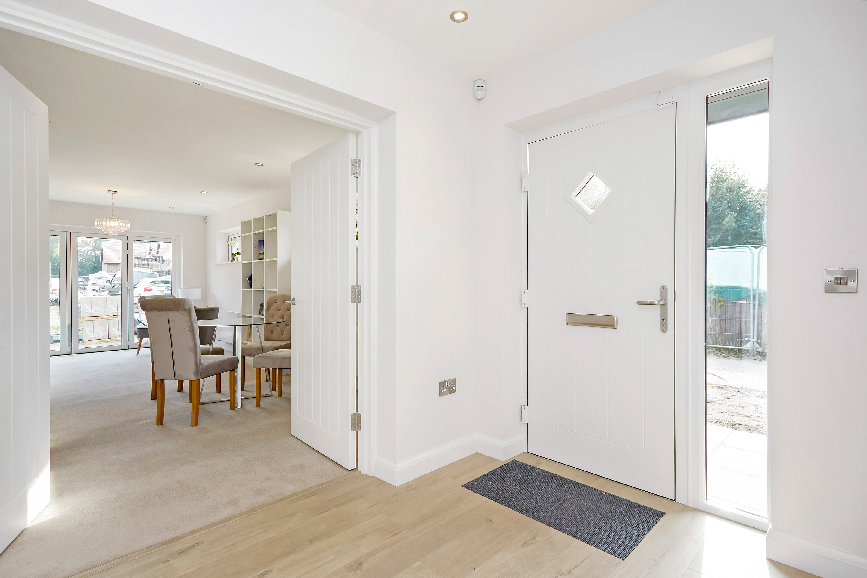 A bright and inviting entrance hall with wood flooring and large double doors opening onto a large dining area.