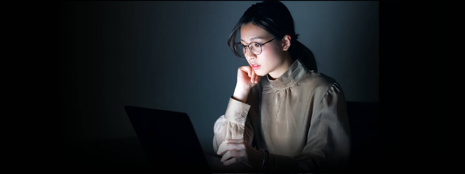 Business woman wearing glasses and checking email on a laptop