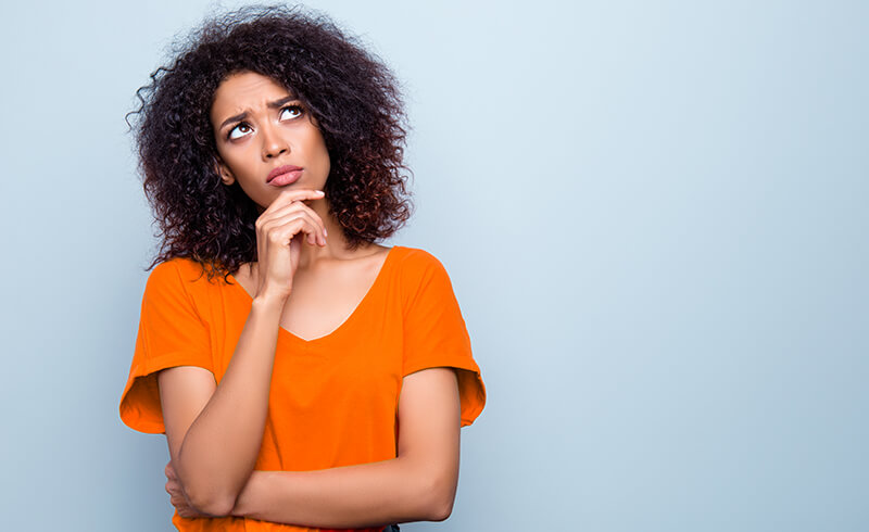 Woman in an orange shirt looking thoughtful with her hand on her chin - eLearning 101: The eLearning Retention Resolution The eLearning Retention Resolution- eLearning Development - Flare Learning