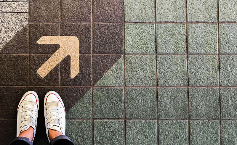 This image shows a birds-eye view of white shoes in the bottom-left  corner. Above the feet, painted on the tiled ground is an arrow pointing up to the top-right hand corner - Navigating Your eLearning Feedback Journey - eLearning Program Development - Flare Learning
