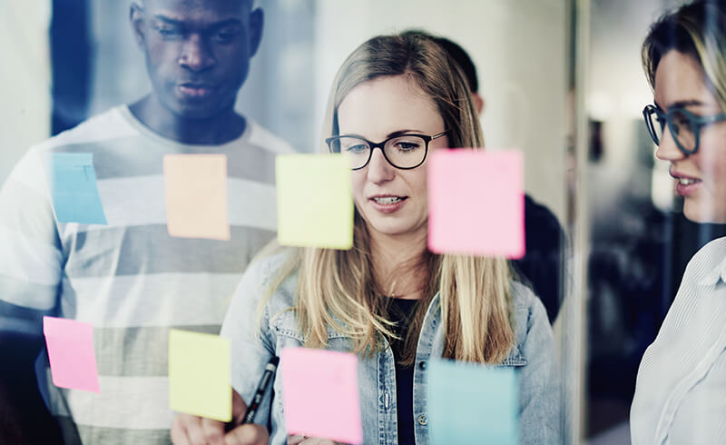 Three work colleagues stand behind a window, looking at a series of colourful sticky notes they've attached to the window.