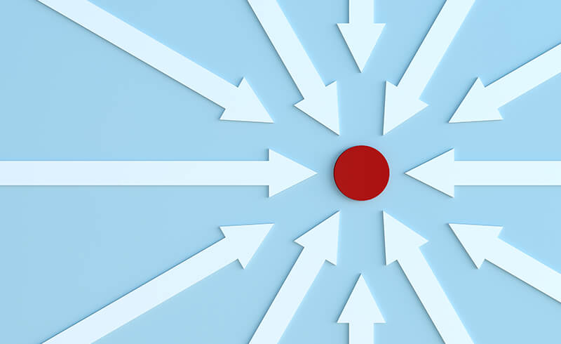 A bunch of white arrows on a blue background circling and pointing to a single red dot.