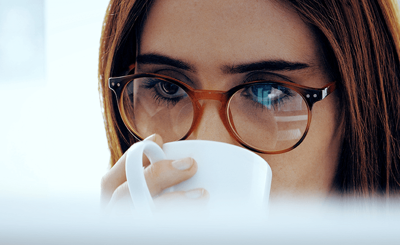 Close-up of a woman's face, with long brown hair and glasses, drinking from a white mug.
