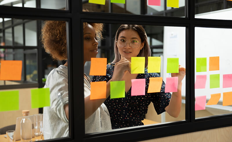 Two women standing behind a window pane that has two rows of coloured sticky notes. They are looking at and writing on the sticky notes.