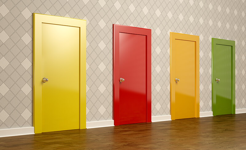 Four colorful doors: one yellow, one red, one orange, and one green. They're all side-by-side, lining a wall.