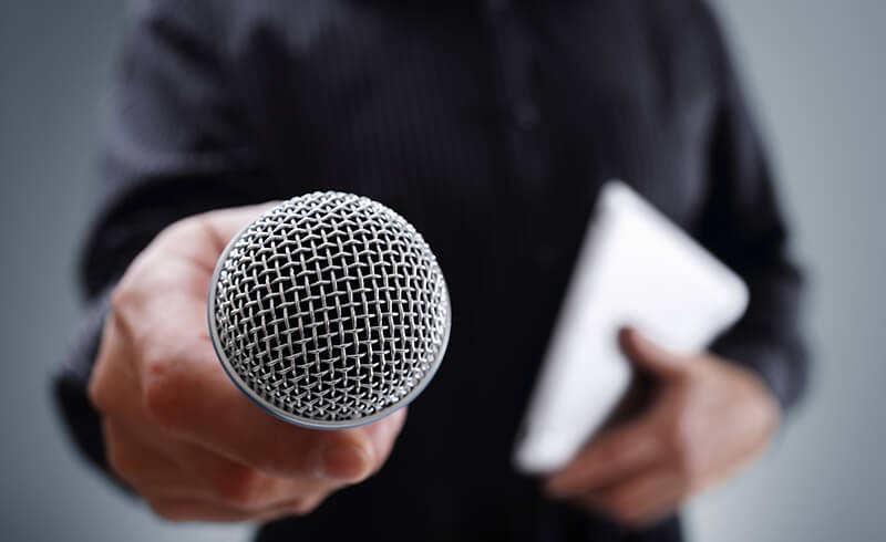Close-up of a microphone being held up by a person as if to interview the viewer.