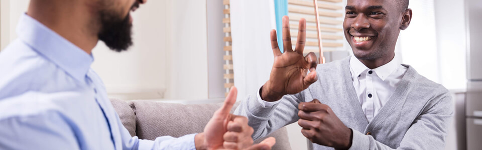 Two men gesturing to each other with sign language.