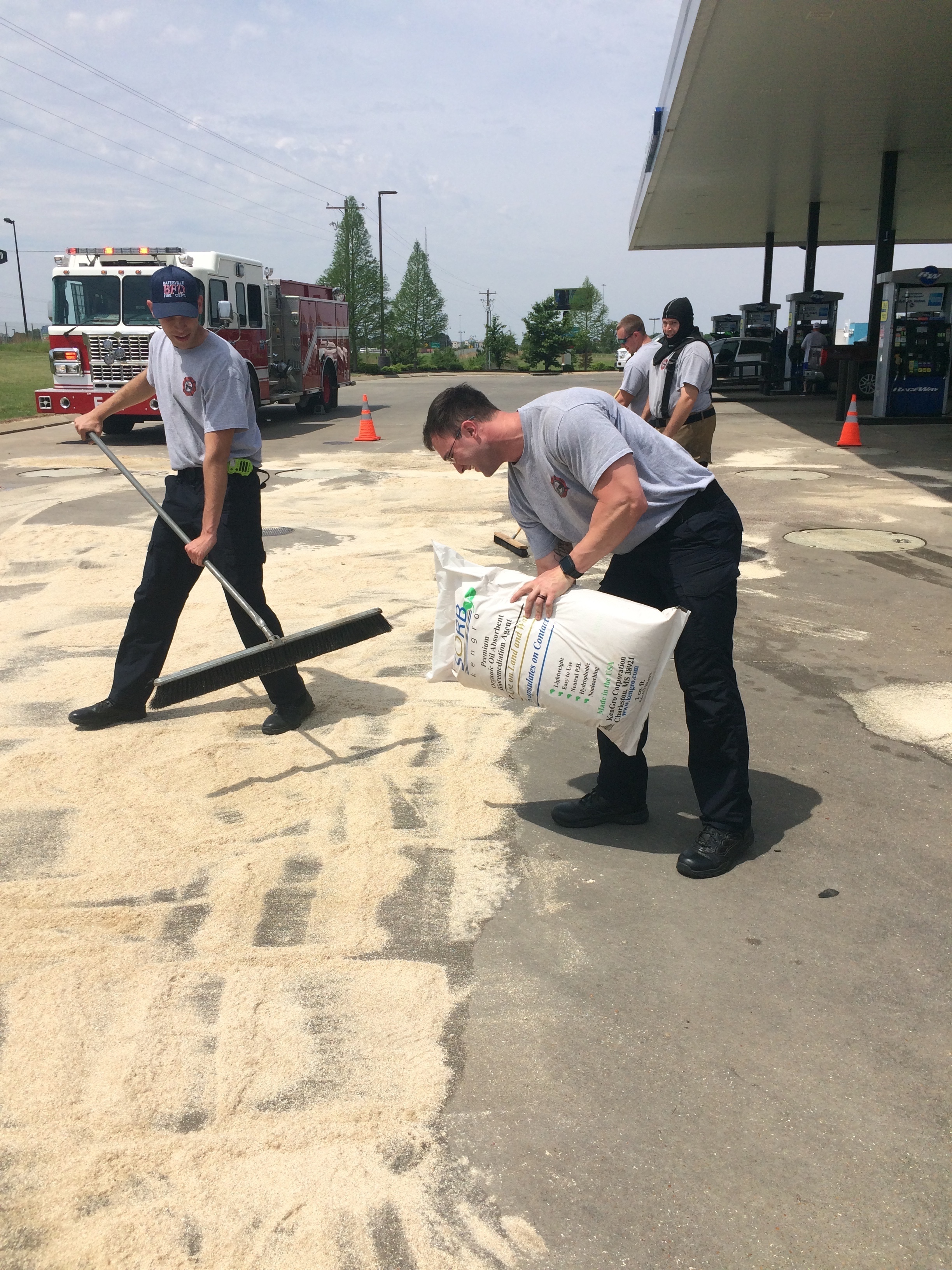 Firemen using Kengro Biosorb biodegradable oil absorbent to clean up a spill.