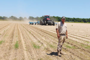Kengro President and CEO Brent Brasher stands in field while kenaf is being planted behind him.