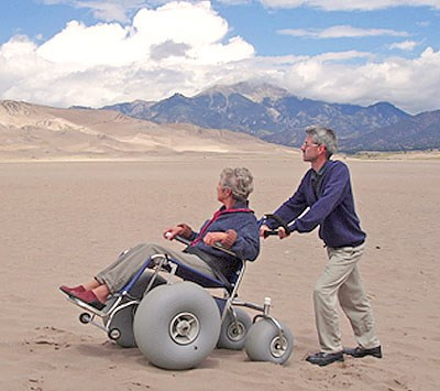 man pushing an accessible sand dune wheelchair in California