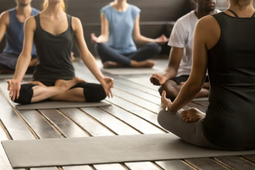 People in a seated yoga position during a class. Yoga is good for ADHD, autism, and many other disorders.