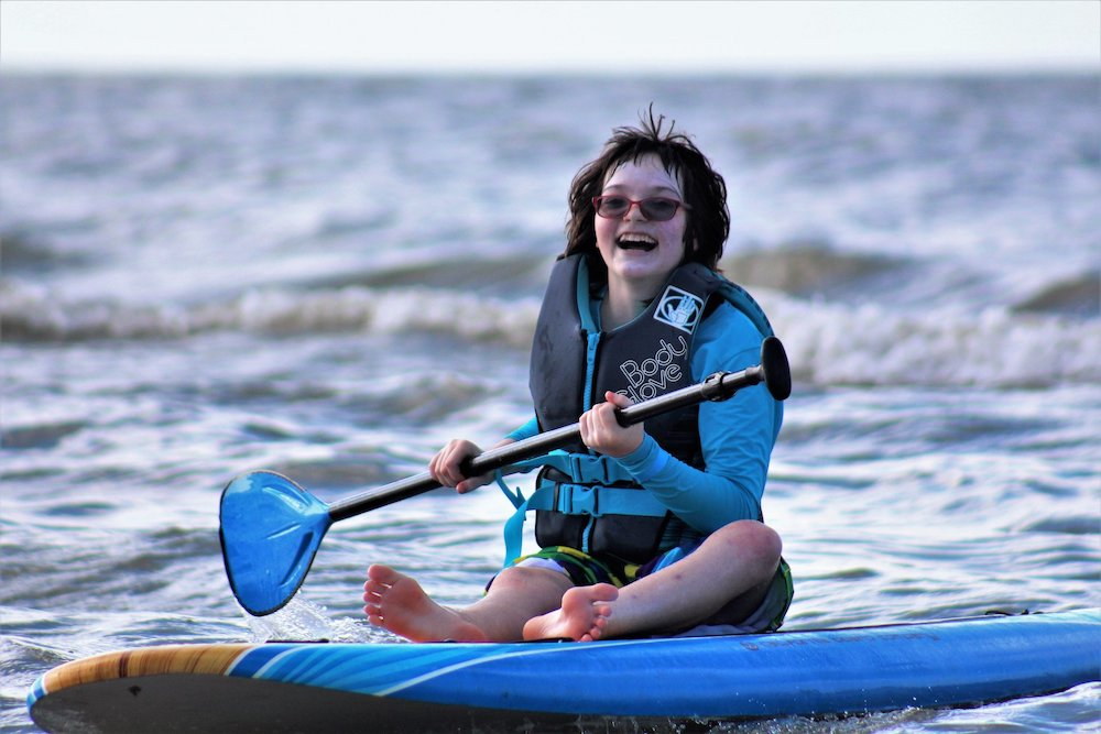 Girl on a paddleboard with surfers for autism
