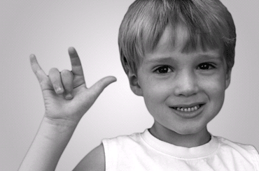 A deaf boy showing the love sign in sign language