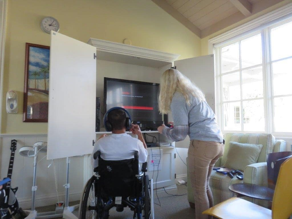 Gamer's Gift charity working with a boy to play videos game from his wheelchair